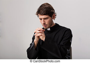 Priest is praying - Young christian priest is saying a...