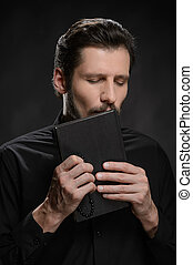 Priest kissing the Holy Bible. Portrait of priest kissing the Holy Bible against black background
