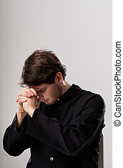 Catholic priest meditating in focus with folded hands