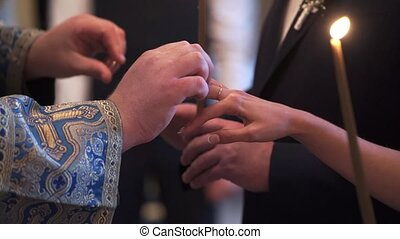 Priest praying in church at wedding ceremony and put on rings for newlyweds