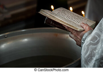 Priest praying in the church holding holly bible and cross with candles