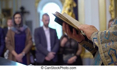 Priest praying with Bible book in church at ceremony