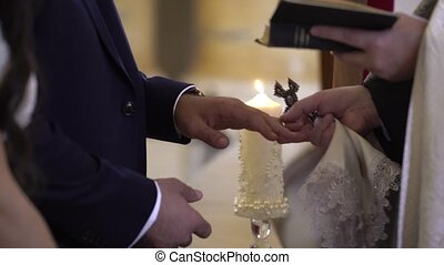 Priest put on wedding rings to bride and groom hands in...