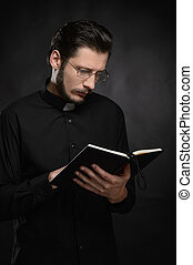 Priest reading the Holy Bible. Portrait of priest reading the Holy Bible