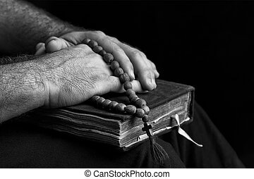Priest with a bible on his knees.