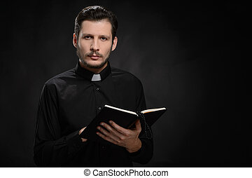 Priest with Holy Bible. Portrait of priest reading the Holy Bible