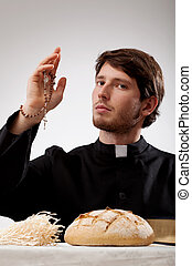 Priest with rosary, bread and the bible