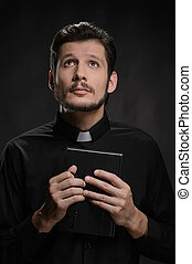 Priest with the Holy Bible. Portrait of priest holding the Holy Bible against black background