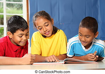 Primary kids learning in classroom - Three happy young...