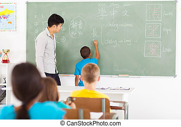 primary schoolboy writing Chinese on the chalkboard -...