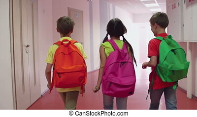 Primary Students - Camera following three kids with...