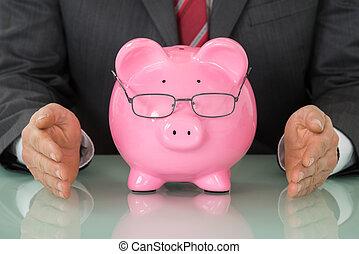 primer plano, de, businessperson, mano, cerca, piggybank rosa, en el escritorio