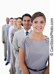 primer plano, de, colegas, en, un, sola línea, sonriente, y, mirar, derecho, con, foco, en, el, primero, mujer, contra, fondo blanco