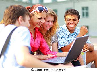 primer plano, de, feliz, joven, amigos, usar la computadora portátil