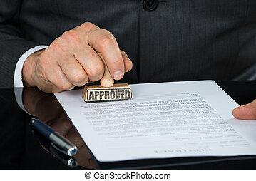primer plano, de, hombre de negocios, mano, estampar, en, aprobado, contrato, forma