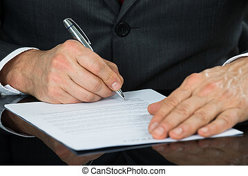 primer plano, de, hombre de negocios, mano que sostiene la pluma, encima, contrato, forma