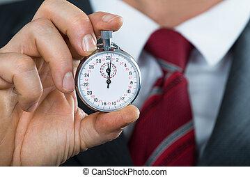 primer plano, de, hombre de negocios, tenencia de la mano, reloj de parada