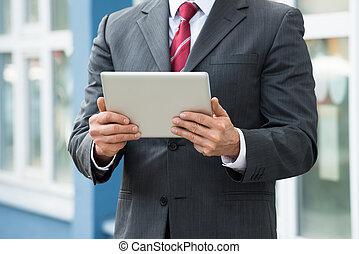 primer plano, de, hombre de negocios, tenencia, tableta de digital