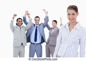 primer plano, de, un, secretario, sonriente, y, empresarios, con, el, pulgares arriba, en, el, plano de fondo