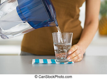 primer plano, en, ama de casa, agua que vierte, en, vidrio, de, filtro del agua, cántaro