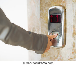 primer plano, en, mujer de negocios, mano, botón elevador que empuja