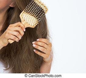 primer plano, en, mujer joven, peinar el pelo
