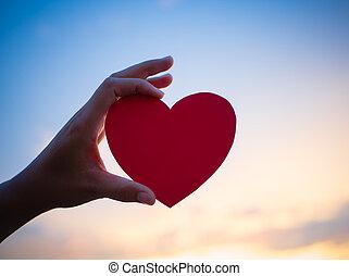primer plano, tenencia de la mano, corazón rojo, durante, ocaso, fondo., feliz, amor, día de valentín, idea, señal, símbolo, concept.