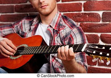 primer plano, virtuoso., pared, joven, guitarra, mientras, propensión, acústico, ladrillo, guapo, juego, hombre