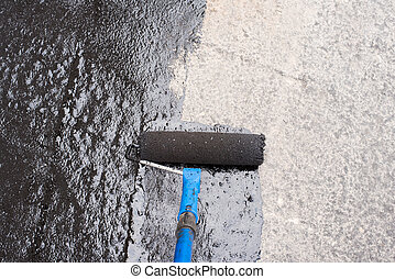 priming concrete screed - Roller brush. Worker covered ...