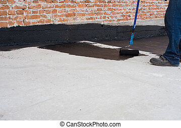 priming concrete screed - Worker covered surface, bitumen ...