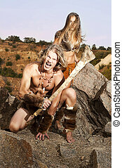 Primitive man holding a club defends his woman. Tribal of a wild people.
