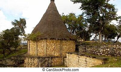 Primitive Peruvian hut, built on hillside - shot taken of...