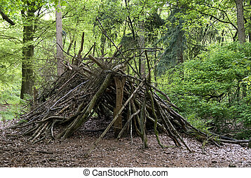 primitive shed in the wood - shelter hut construction of...