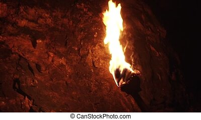 Primitive Torch in Cave - A burning wood made primitive...