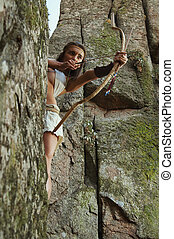 Primitive woman standing on a rock and holding a bow. Amazon...