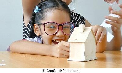 primo piano, colpo, asiatico, piccola ragazza, in, tailandese, asilo, studente, uniforme, e, lei, gioco madre, taglio, di, bianco, fabbricazione carta, famiglia, forma, padre, madre, figlio, e, figlia, su, tavola legno