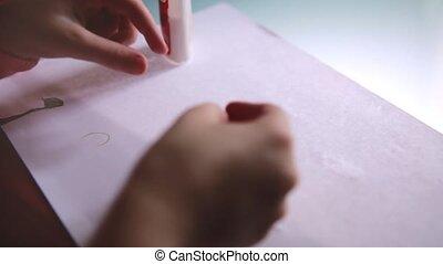 primo piano, colpo, di, poco, ragazza, mani, in, maglione rosa, creare, divertente, carattere, forme, da, carta, e, colla, su, uno, tavola.