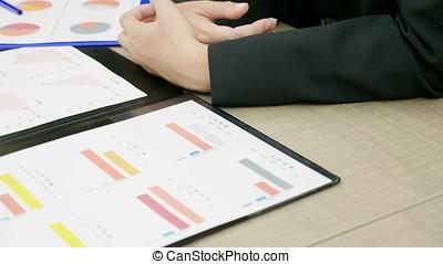 primo piano, di, businesspeople, a, uno, scrivania, ufficio, parlare, e, analizzare, finanziario, tabelle