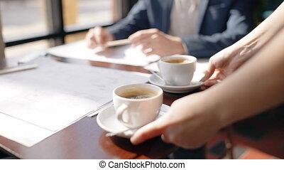 primo piano, di, cameriera, mani, mettere, due, campanelle, di, caffè, a, il, tavola, davanti, architetto, lavorando, casa, blueprint.