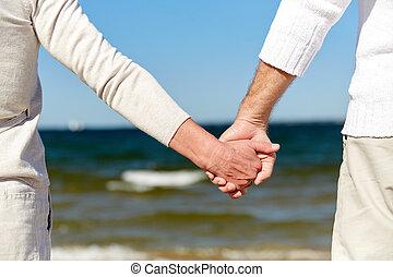 primo piano, di, coppie maggiori, tenere mani, su, spiaggia