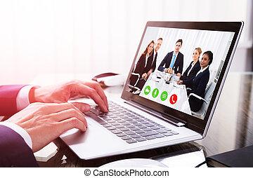primo piano, di, uno, businessperson's, mano, conferencing video, su, laptop