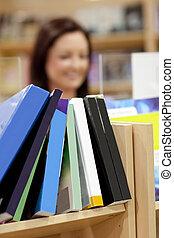 primo piano, di, uno, mensola libro, in, uno, biblioteca, con, femmina, cliente, in, il, fondo