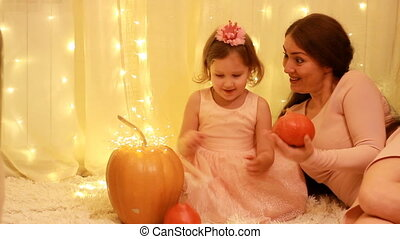 Princess child girl with Mother playing with pumpkins and in...
