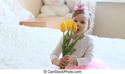 Princess girl with yellow tulips in hands