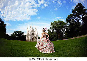 Princess in an vintage dress before the magic castle