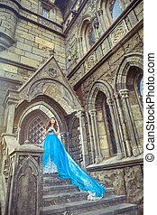 Princess in blue dress is going to open the castle door.