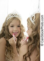 princess little girl painting makeup lipstick on mirror