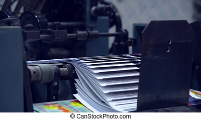 printing house equipment - newspaper moving on conveyor belt