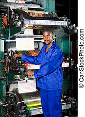 printing press operator - african man operating printing...