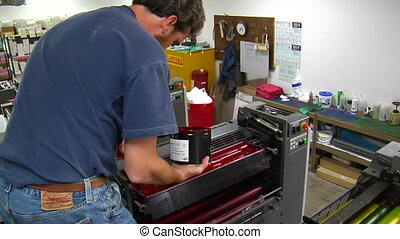 printing press technician adds red ink